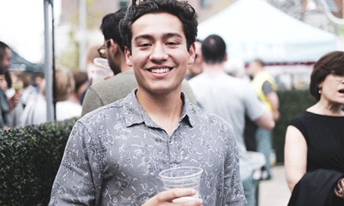 person at a party holding a drink and smiling