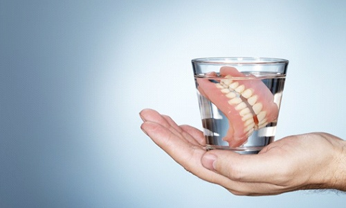 hand holding glass of water with full dentures