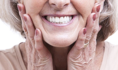 close up of older woman smiling and holding her face