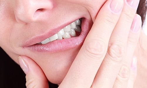 Closeup of person holding mouth in pain