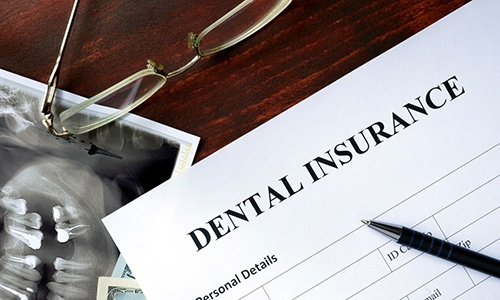 a blank dental insurance form with a pen sitting on top of it