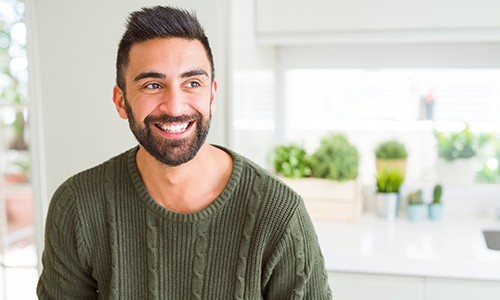 person smiling and sitting in a kitchen with a sweater on