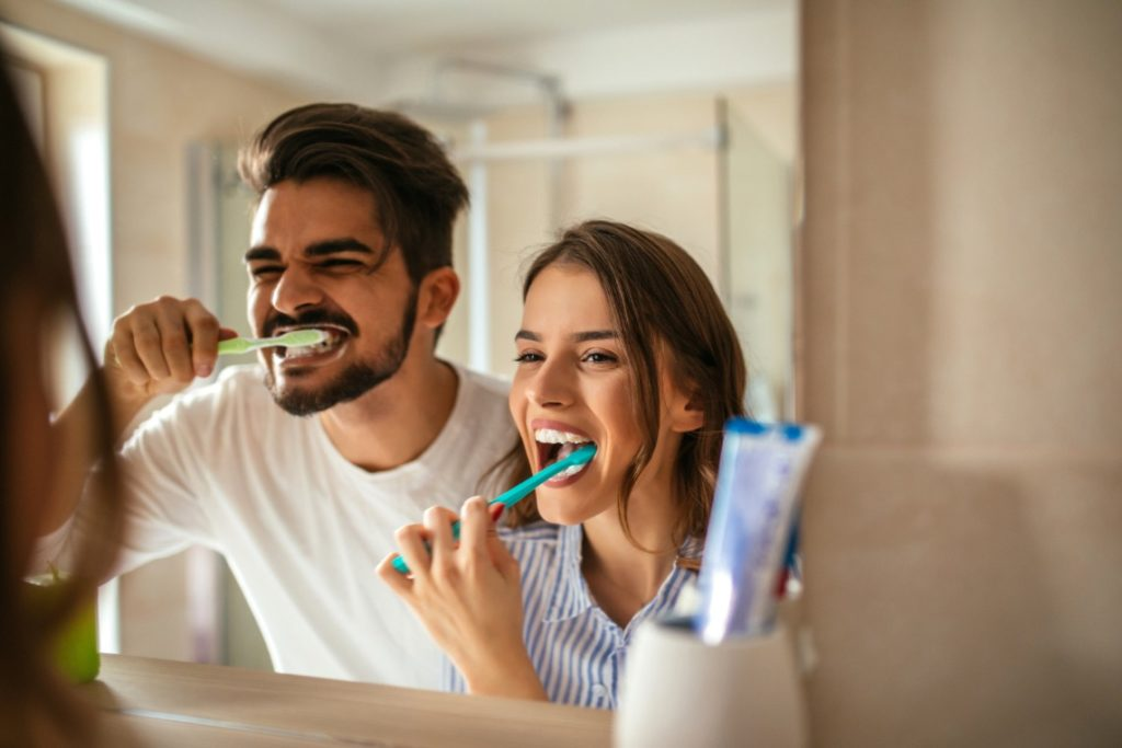 Man and woman brushing their teeth with tips from the dentist in Worcester