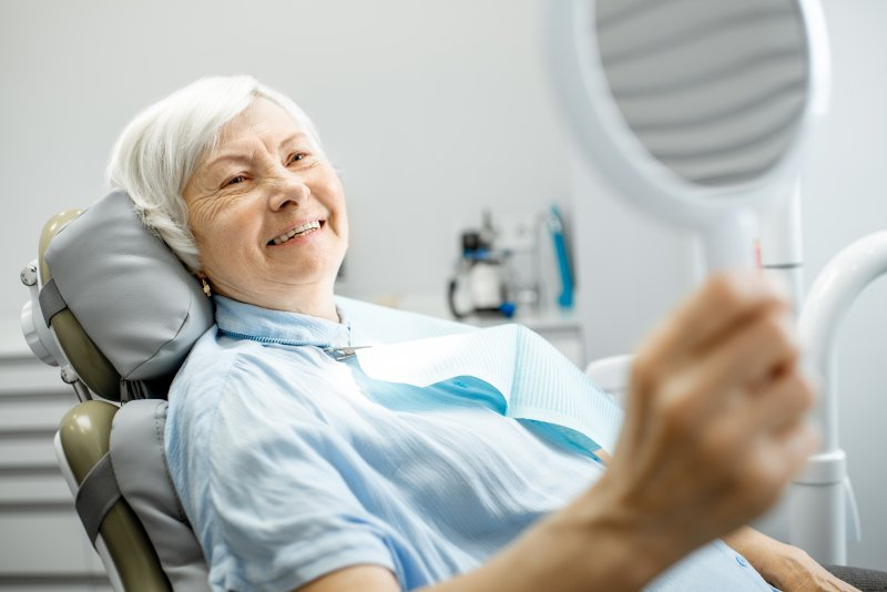 Elderly woman smiling with dental implants