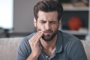 Pained man with cavity touching his cheek